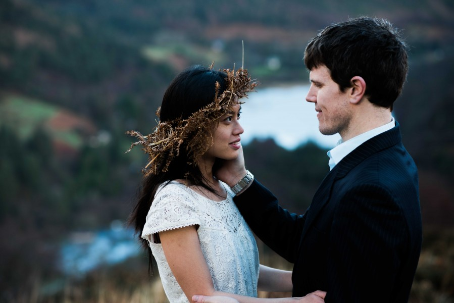A Khmer Cambodian American young woman stands with her Irish husband in the hills mountains of Glendalough, Ireland. Her head is covered in a homemade wreath and he is wearing a suit in the cold weather. They clearly love each other during this engagement photo shoot.