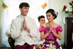 A Khmer Cambodian Wedding in Philadelphia, Pennsylvania, USA. The outfits are incredibly colorful, ornate and covered in gold jewelry and belts. The bride, dressed in pink, and the Irish groom, dressed in white and pink, smile during one of the many ceremonies of the day.