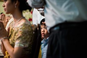 A Khmer Cambodian Wedding in Philadelphia, Pennsylvania, USA. The outfits are incredibly colorful, ornate and covered in gold jewelry and belts. A young boy looks on as his father participates in the traditional haircutting ceremony for the bride.