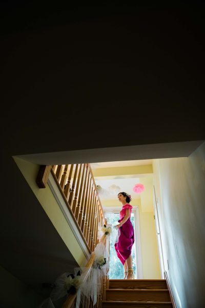 A Khmer Cambodian Wedding in Philadelphia, Pennsylvania, USA. The outfits are incredibly colorful, ornate and covered in gold jewelry and belts. The bride stands at the top of the stairs in her pink outfit waiting for the sound of the gong before going downstairs for one of many ceremonies.