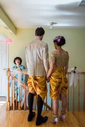 A Khmer Cambodian Wedding in Philadelphia, Pennsylvania, USA. The outfits are incredibly colorful, ornate and covered in gold jewelry and belts. The bride and groom, both dressed in golden yellow, talk with the mother of the bride upstairs between ceremonies.