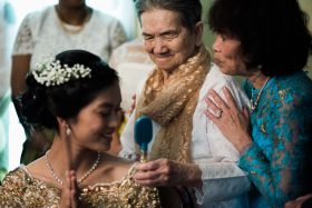 A Khmer Cambodian Wedding in Philadelphia, Pennsylvania, USA. The outfits are incredibly colorful, ornate and covered in gold jewelry and belts. Three generations of cambodian American women share a moment during the haircutting ceremony in their home.