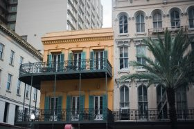 A traditional classic new orleans french quarter yellow hotel with blue window shutters and metal rail balcony. A palm tree stands in front of another motel hotel in Louisiana, USA