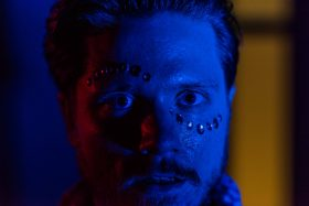 dilated, dilated pupils, large pupils, glitter, jewels, face, portrait, color, red light, blue light, dance, club nightlife, time, perception, Amsterdam, netherlands, Dutch, man, photography, photo series