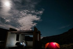 The best camping spot at a canyon in southern Colorado. The moon and stars are in the sky, the orange and red tent is glowing and a man cooks dinner on the camping stove under an adobe hut.