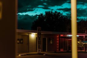 The Route 66 Motel off of the highway in New Mexico, USA, America. The sunset colors are a deep turquoise blue against the yellow and pink lights of the motel.