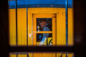 A train conductor checks tickets and gives information on the yellow and blue classic Silverton Durango steam train in Colorado, USA, America.