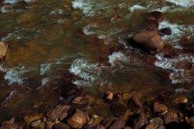 Water flows over red rocks in the riverbed in Durango, Colorado, USA.