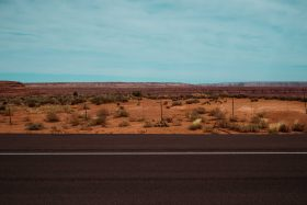 Roadside view in Monument Valley, Utah, USA. The road meets the red dirt desert then touches the clear blue sky.