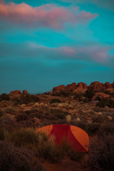 An orange and red tent is pitched at campsite in Arches National Park, moab, Utah, USA at sunset with pink and blue sky. The campground is the only one inside the park and spaces are limited and serene, peaceful, quiet and amazing.
