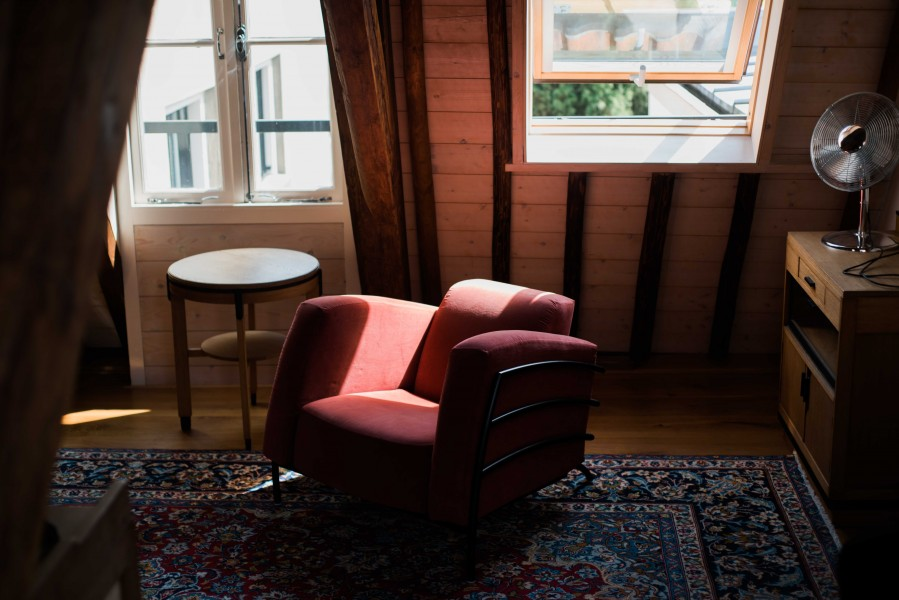 A red chair sits empty and in the slice of sun in an apartment in Utrecht, the Netherlands.