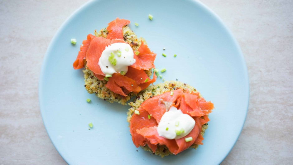 A yummy blue plate of salmon quinoa breakfast cakes with poached eggs and creme freche.